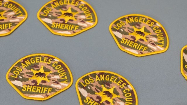 several los angeles county sheriffs department patches on a neutral grey background