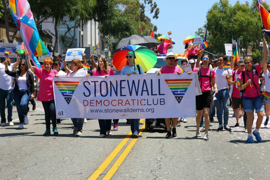 """Stonewall Democratic Club members wear colorful clothing, wave rainbow flags and hold a large banner that reads """"Stonewall Democratic Club"""" as the march down the street during Pride 2021."""